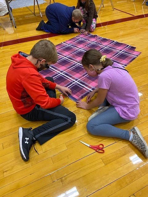 Students working together to measure and cut their homemade blankets