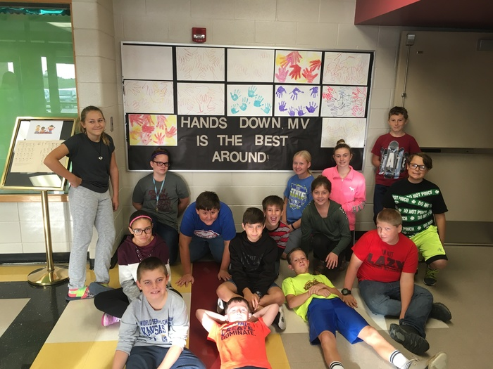 Sixth Grade students working on the elementary bulletin board