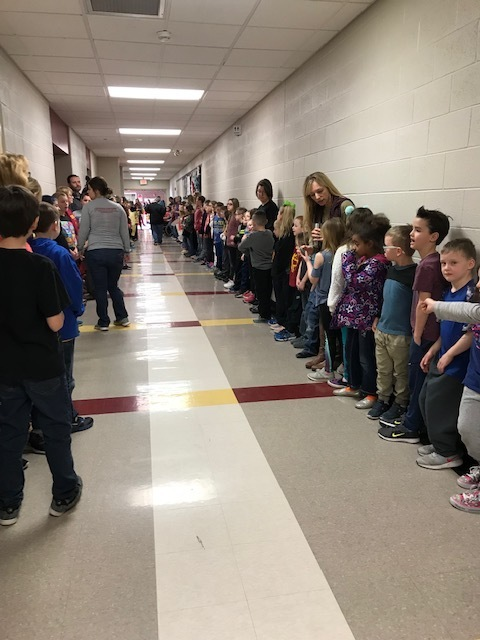 Elementary students lining the halls to cheer the basketball players on