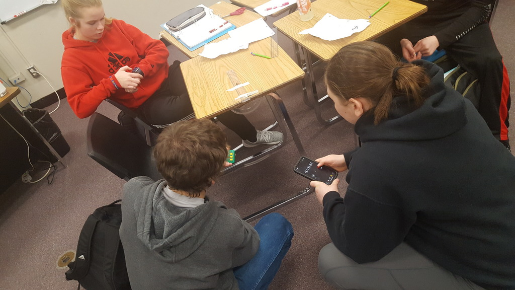 Students testing the swing of a pendulum in Math 1